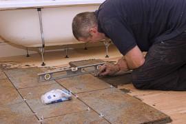 Specialist met gereedschap legt vloertegels © Paul Murphy - Fotolia